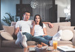 Full length portrait of surprised young couple is watching movie together at home. They are looking forward with shock while sitting on couch and embracing