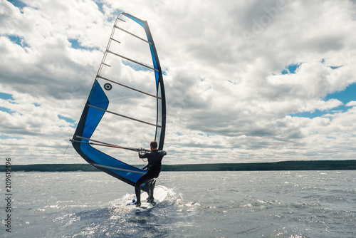 the guy in the waggon swims on the windsurf on   lake