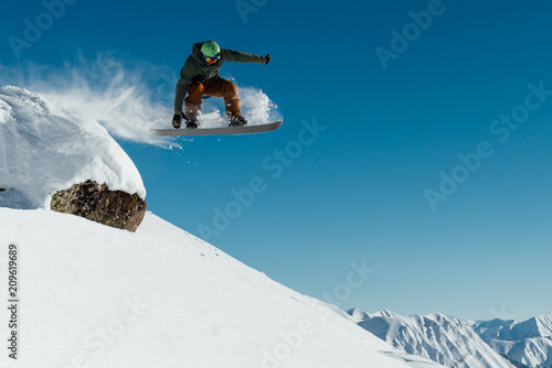 plakat snowboarder in the outfit drops off the ledge of the stone onto the fresh snow creating a spray of snow
