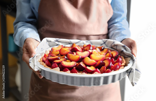 Woman holding delicious pie with plums, closeup