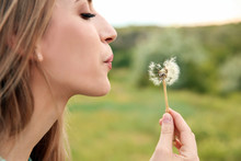 Attractive Young Woman Blowing Dandelion Flower Outdoors
