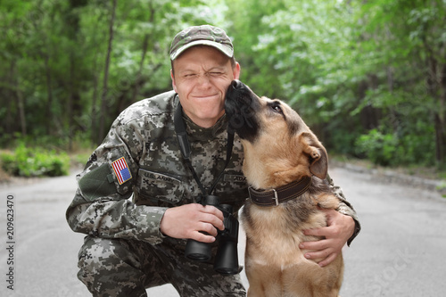 Photo Man in military uniform with German shepherd dog, outdoors