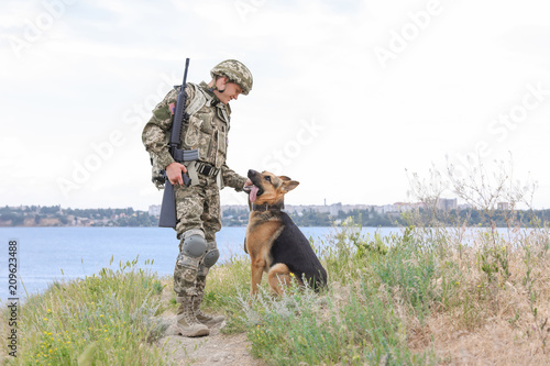 Poster Chasse Man in military uniform with German shepherd dog near river