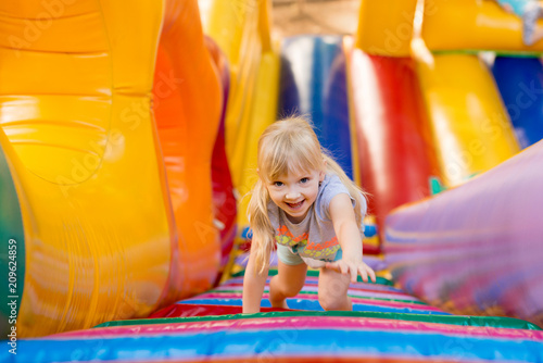 Poster Attraction parc happy excited girl having fun on inflatable attraction playground.