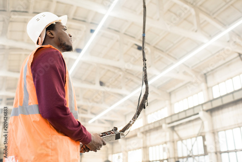 Photo Serious skilled construction engineer in hardhat and vest using crane controller