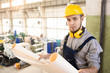 Content confident handsome young bearded male construction worker in hardhat and soundproof headphones analyzing blueprint and looking at camera