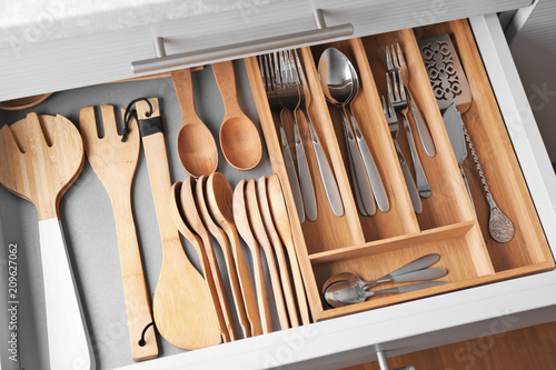 Set of cutlery and wooden utensils in kitchen drawer
