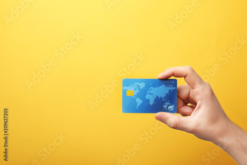 Cuadros en Lienzo Young man holding credit card on color background