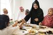 Leinwanddruck Bild - Muslim woman sharing food at Ramadan feast