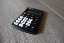 Black Pocket Calculator On White Wood Table