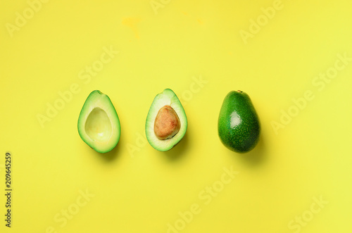 Fotografie, Obraz  Organic avocado with seed, avocado halves and whole fruits on yellow background
