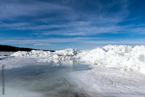 Poster Donkergrijs frozen lake covered with stack of ice floes and blue sky
