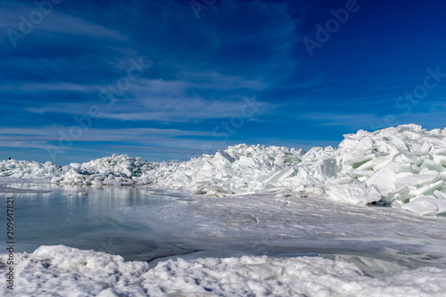 Deurstickers Donkergrijs frozen lake covered with stack of ice floes and blue sky