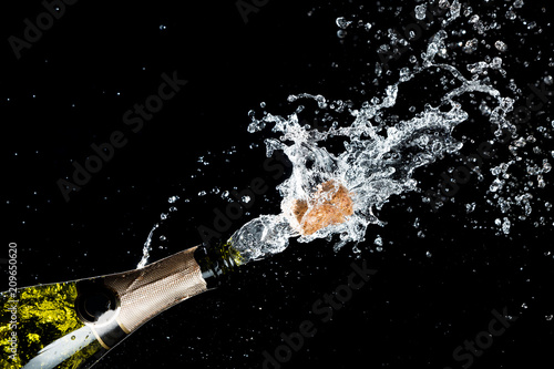 Celebration of birthday, anniversary or Christmas theme. Explosion of splashing champagne sparkling wine with flying cork out of the bottle on black background.