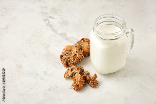Fototapeta Delicious oatmeal cookies and mason jar with milk on light background