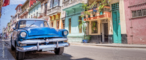 Photo Stands Retro Vintage classic american car in a colorful street of Havana, Cuba. Panoramic travel photography.