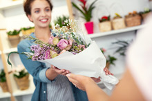 Nice Bouquet. Selective Focus Of Flowers Being Given To A Nice Pleasant Woman By A Shop Assistant