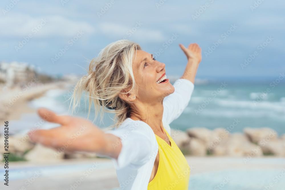 Fototapeta ältere Frau steht mit ausgebreiteten armen am strand und genießt den Urlaub