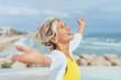 canvas print picture - ältere Frau steht mit ausgebreiteten armen am strand und genießt den Urlaub