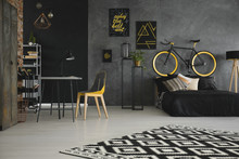 Patterned Carpet In Teenager's Room Interior With Yellow Chair At Desk And Bike Above Bed. Real Photo