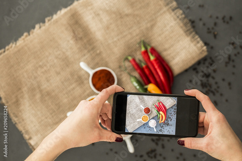 In de dag Aromatische Woman taking a photo of chili peppers and spices with smartphone