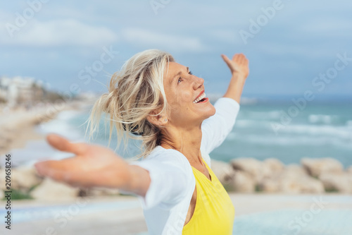 Cuadros en Lienzo ältere Frau steht mit ausgebreiteten armen am strand und genießt den Urlaub