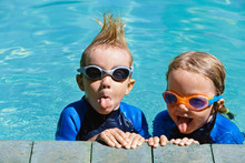 Happy Children In Wetsuits And Goggles Learn To Swim, Have Fun At Poolside In Outdoor Pool. Healthy Family Lifestyle, Little Kids Water Sports Activity, Swimming Lessons With Parents At Training Class