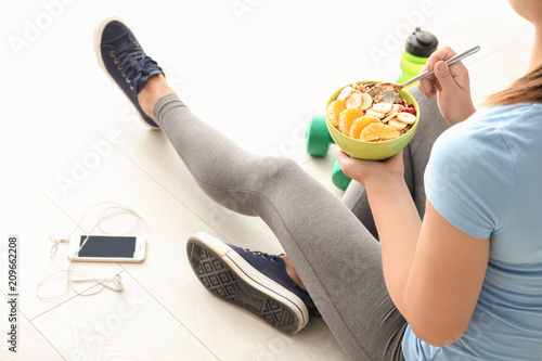 Photo Sporty young woman with bowl of tasty oatmeal at home