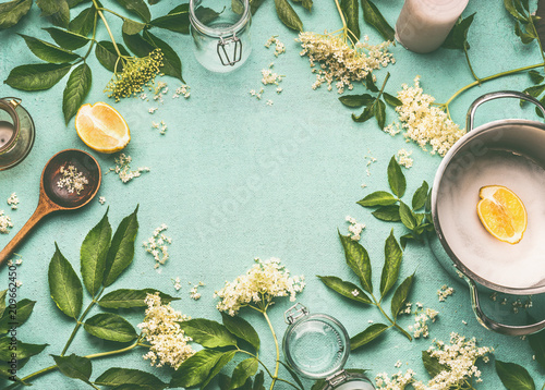 Fototapeta Elder flowers  cooking preparation. Frame of Elder flowers with spoon, pot, sugar and lemon on blue table background, top view obraz