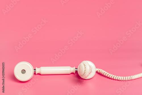 Retro biały telefon na różowym tle
