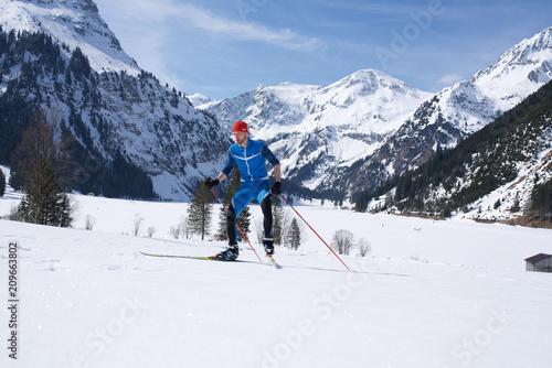 Skilangläufer vor Alpenbergen im Winter beim Skifahren