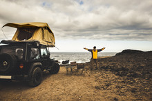 Adventurer Man In Journey Travel With Off Road Car And Roof Tent To Enjoy Freedom And Explorer Concept. Discover The World Living Near The Power Of The Nature. Ocean Coast Home View.