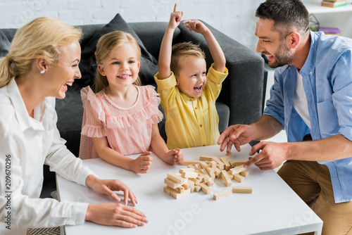 Obraz happy family playing with wooden blocks at home - fototapety do salonu
