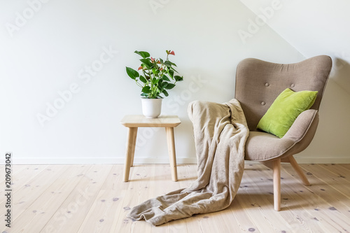 Valokuva Beige armchair with a green pillow, blanket and a wooden table with a potted plant (Anthurium)
