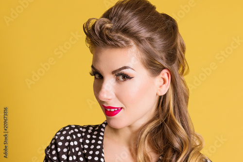 Fotografía  Beautiful woman with make up poses in yellow studio, pin up style