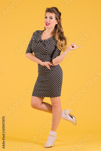 Young woman in dress with hairdo poses in yellow studio, pin up style full body