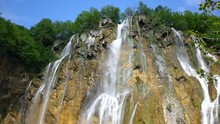 Looking Up At A Tall Waterfall As Water Rushes Over Rocks In Slow Motion