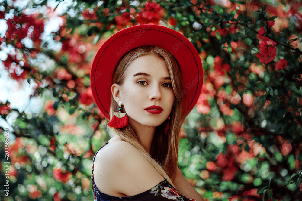 Fototapeta Outdoor portrait of young beautiful girl with red lips, long blonde hair, wearing hat, long tassel earrings, cold shoulder dress, posing near blooming tree. Summer fashion concept. Copy space