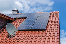 Red Tiled Roof With Solar Panesl Or Photovoltaic Plant And Satellite Dish