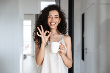 Portrait Of Caucasian Curly Woman With Long Dark Hair Smiling At Camera, And Showing Ok Sign, While Drinking Tea At Hotel Apartment Or Flat In Morning