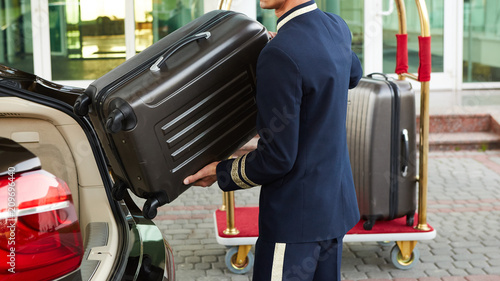 Fotografía Bellboy taking baggage of guest from thee car to his room