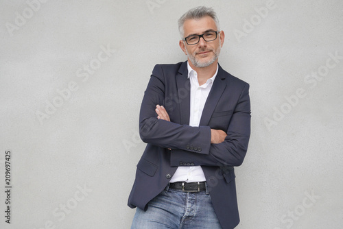 Fotografía  Businessman leaning on concrete wall, isolated