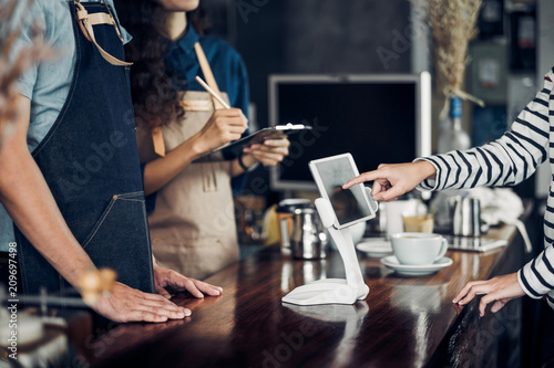 Tuinposter Restaurant customer self service order drink menu with tablet screen at cafe counter bar,seller coffee shop accept payment by mobile.digital lifestyle concept.Blank space for display of design.