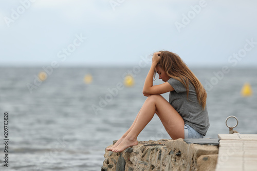 Poster Hoogte schaal Sad teen alone with ocean in the background