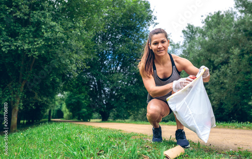 Fotografie, Obraz  Girl crouching with garbage bag looking camera doing plogging outdoors