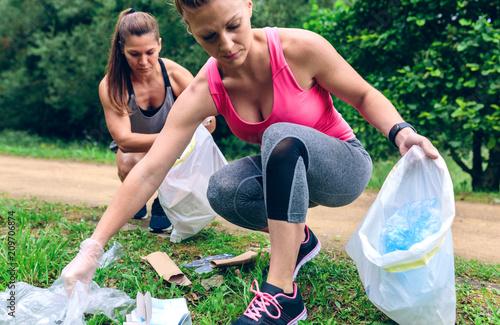 Fotografía  Women crouching with bag picking up trash doing plogging