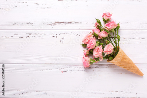 Pink roses flowers in waffle cone on  white wooden background.