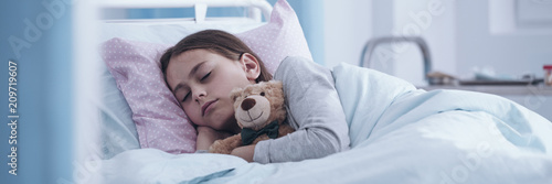 Panorama portrait of a sick little girl sleeping in a hospital bed with a teddy Fototapet