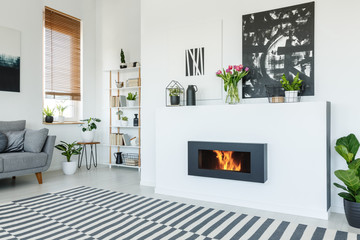 Black painting above fireplace in white living room interior with patterned carpet and grey sofa. Real photo