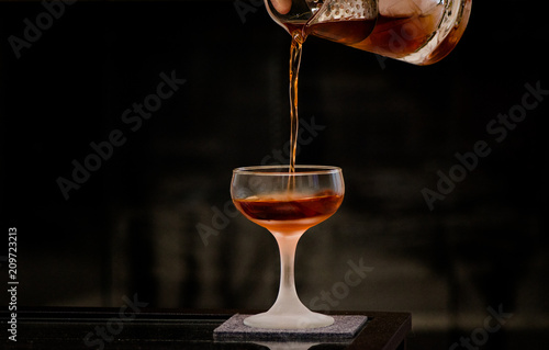 Pouring cocktail into coupe